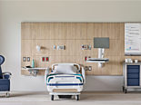 Healthcare headwall with recliner, medical cart, and medical storage.