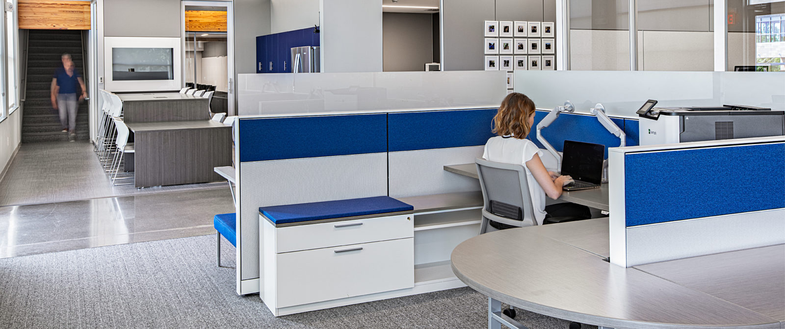 Open workstation with high performance office chair. Adjacent to a breakroom featuring barstools, custom millwork, and embeded technology.