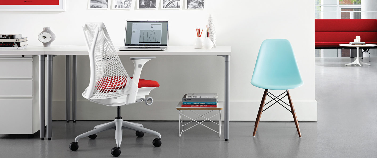 Individual workstation with ergonomic office chair and Eames molded plastic side chair.