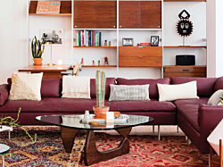 An eclectic lounge setting featuring a plum colored Herman Miller Bolster Sofa, Noguchi Table, and Nelson CSS Wall System.
