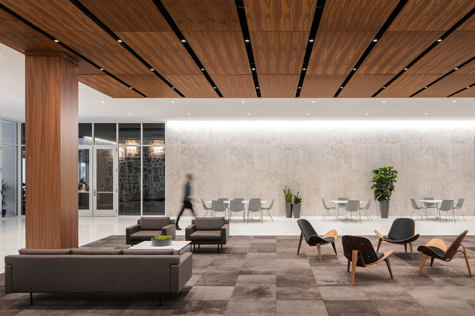 Corporate office lobby in downtown Des Moines, IA. Guest seating and lounge seating surrounded by warm woods and dark hues.