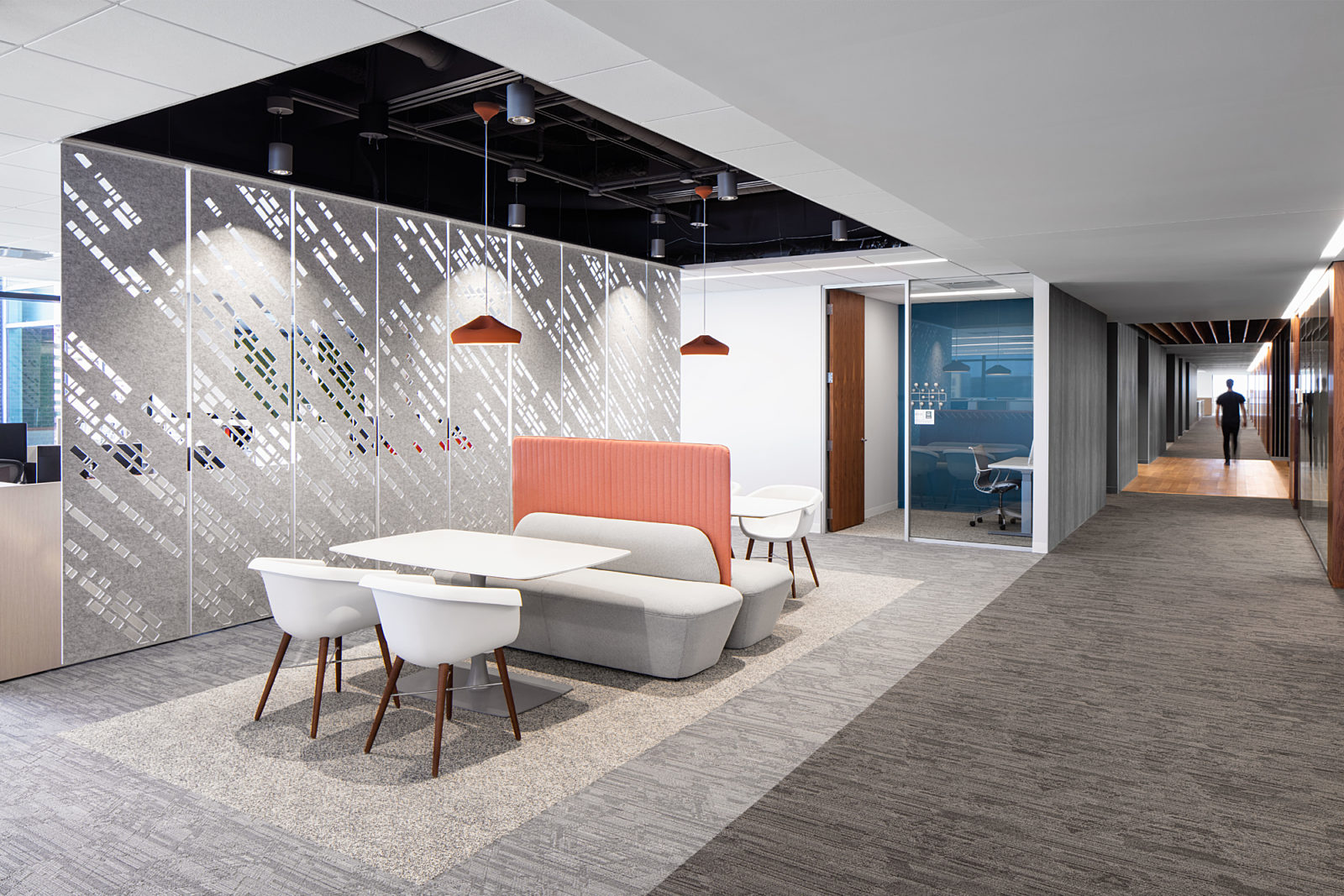 Modern office with booth seating. Acoustical tiles and room divider. Hallway leading to conference room.
