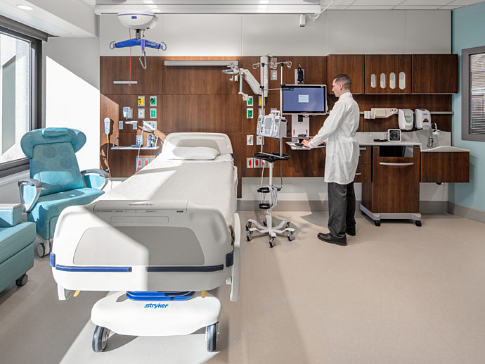 Patient room with patient seating and clinical casework.